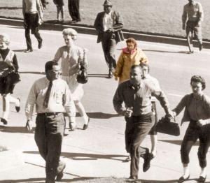 Lady Babushka, coloreada, corre junto con el resto de los presentes hacia la plaza Dealey